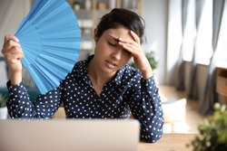 Tired overheated young indian woman hold wave fan suffer from heat sweating indoor work on laptop at home office, annoyed girl feel uncomfortable hot summer weather problem no air conditioner concept