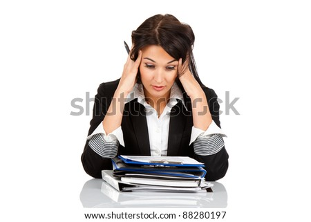 tired overworked business woman sitting at the desk with folder stack holding head with hands. Isolated on white background.
