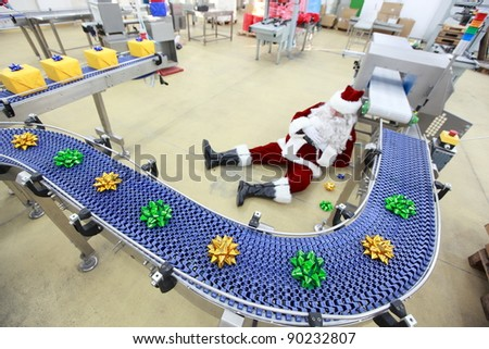 Tired overworked santa claus lying on the floor at the  presents production line in factory