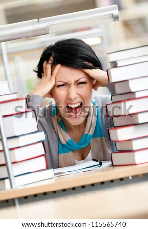 Tired pretty woman with headache sitting at the desk surrounded with piles of books