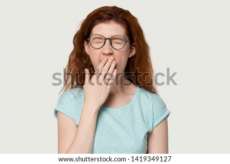 Tired red-headed woman in glasses closed eyes cover mouth with hand yawning feels weak bored pose on grey white background, studio head shot. Chronic fatigue syndrome, lack of sleep and energy concept