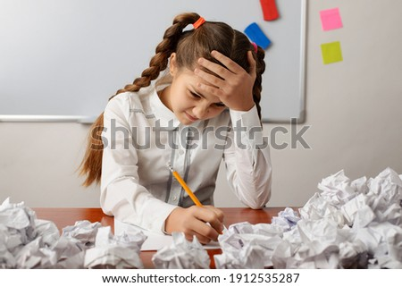 Tired school girl writing something, doing a difficult task bored of constant education. Little girl trying to do a home assignment, thinking hard Foto d'archivio ©