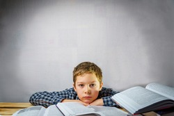 Tired schoolboy thinks lying on the table among the books. World Book and Copyright Day Free space for writing text