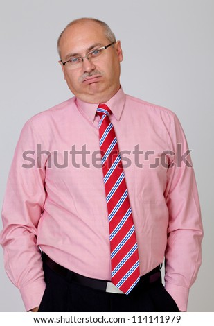 Tired senior businessman in a shirt and tie with hands in the pockets isolated on grey