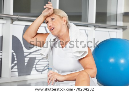 Tired senior woman wiping sweat of her forehead in gym