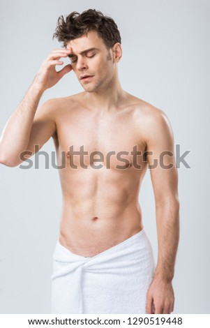 tired shirtless man posing in towel having headache isolated on grey