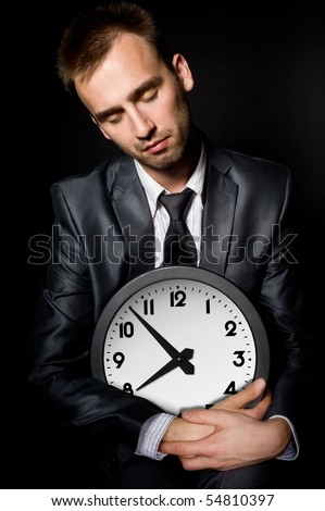 tired sleeping businessman holding clock, over black