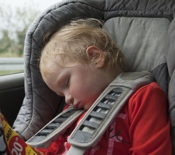 tired sleeping child in car seat