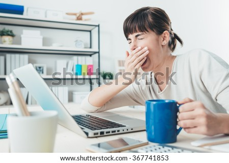 Tired sleepy woman yawning, working at office desk and holding a cup of coffee, overwork and sleep deprivation concept
