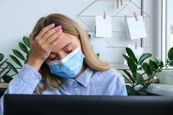 Tired sleepy young caucasian woman worker wearing medical face mask at desk workplace. Overworking and sleeping deprivation. Headache Freelancer in depression. Cold and sick at workspace