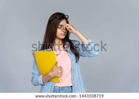 Tired stressed indian young woman student feel hurt eye strain headache from glasses isolated on grey studio background, copy space, dry eyes fatigue, bad eyesight vision problem tension concept
