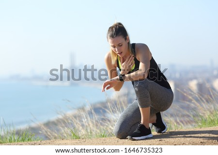 Photo of  Tired stressed runner controlling pulsations checking smartwatch after exercise in city outskirts
