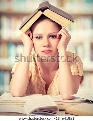 tired student girl learning: writing, reading books - stock photo