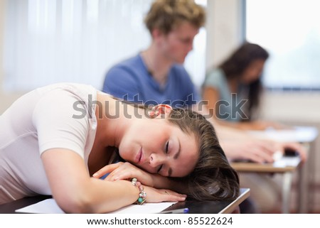 Tired student sleeping in a classroom