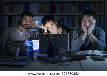 Tired students studying late at night, they are staring at the laptop screen and falling asleep