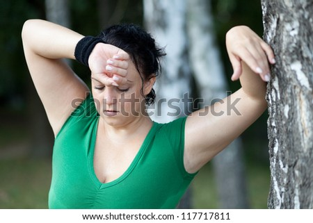 Tired sweaty overweight woman catching her breath after training - stock photo