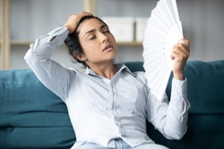 Tired sweaty young indian woman holding using hand fan sit on couch in uncomfortable hot summer weather suffer without air conditioner cooling feel hot at home apartment, overheating concept