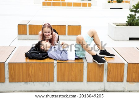 Tired teenager schoolboy sleeps after class in schoolyard of campus on wooden bench, schoolbag under his head. girl looks at him in love. School love concept Stock photo ©