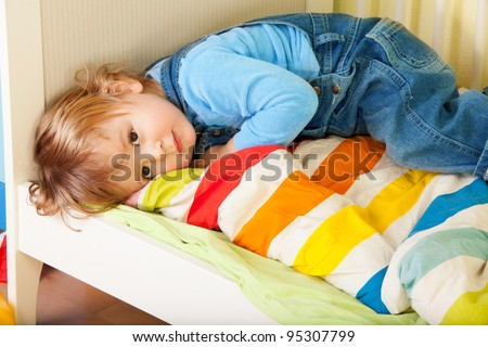Tired toddler laying in his bed on a stripped blanket