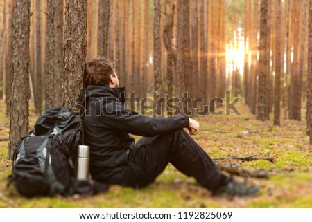 Tired tourist is resting in the forest. Traveler man at halt. Copy space