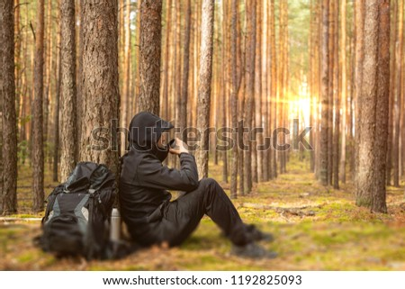 Tired tourist is resting in the forest. Traveler man at halt drinks from a thermos. Copy space