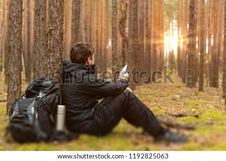 Tired traveler man at halt with smartphone in hand is looking for the right way. Tourist is resting in the forest. Copy space