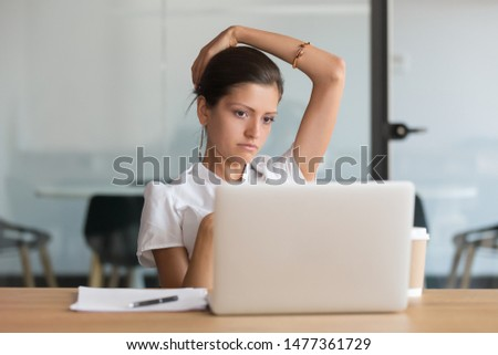 Tired unmotivated woman office worker sit at desk look at laptop screen think about problem solution, search approach inspiration feeling bored of monotonous work. Lack of motivation, dead end concept