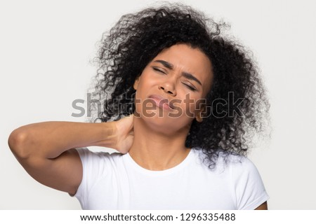 Tired upset african young woman massaging hurt stiff neck isolated on white grey studio background, fatigued sad black lady rubbing tensed muscles to relieve joint shoulder pain, fibromyalgia concept