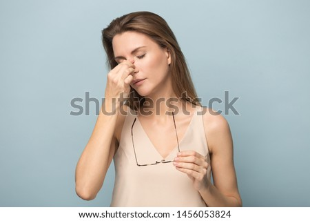 Tired upset woman taking off glasses, suffering from eye strain, tired student, businesswoman with closed dry irritable eyes massaging nose bridge, fatigue, isolated on studio background