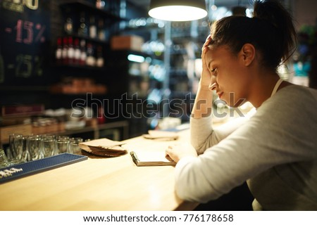Tired waitress reading notes about orders and tips at the end of working day