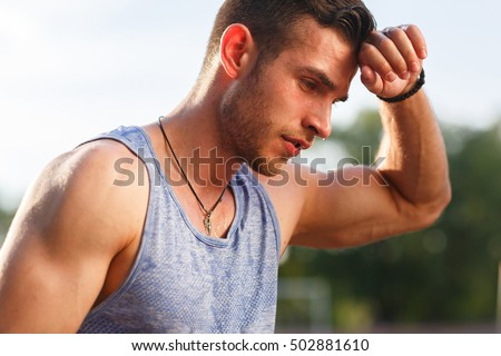 Tired wet athletic man wiping sweat his hand