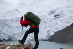 Tired woman backpacker hiking in high altitude winter mountains