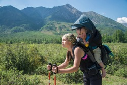 Tired Woman Hiker trekking in mountains with child in backpack, stopped for rest. Mother with baby boy travelling in summer sunny day.
