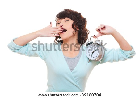 tired woman holding alarm clock and yawning. isolated on white background