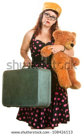 Tired woman in polka dot dress with teddy bear and suitcase