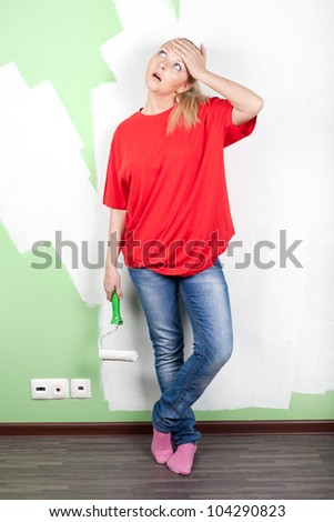 Tired woman in red t-shirt with paint roller near green wall