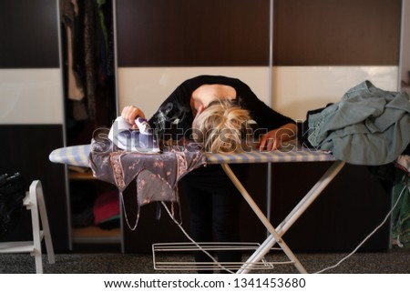 Tired woman ironing is head on ironing board while the iron burns the laundry #1341453680