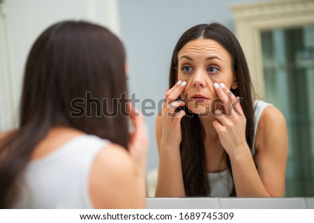 Tired woman looking at her eye bags in the bathroom.