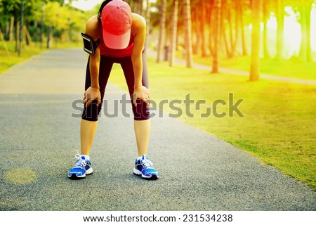 tired woman runner taking a rest after running hard in tropical park trail