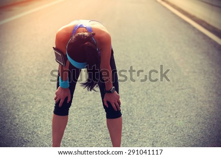 tired woman runner taking a rest after running hard on city road