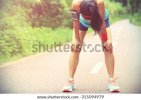 tired woman runner taking a rest after running hard on forest trail