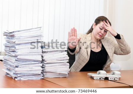 Tired woman sitting at the table in working place in office room