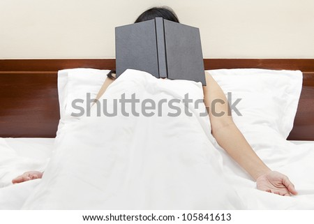 Tired woman sleeping on the bed after read a book with face covered by the book