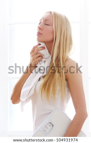 Tired woman with towel after fitness workout