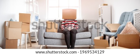 Tired womanwith cardboard box on her head sitting on the sofa in her new house.