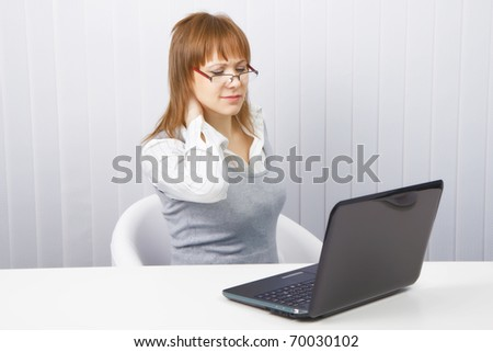 tired worker in the office. Disheveled girl with laptop. neck pain