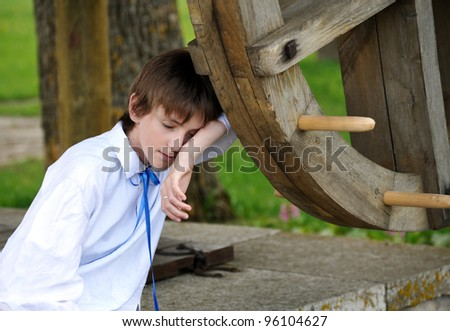 tired young boy sitting on the well #96104627
