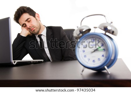Tired young business man sleeping next to his laptop computer at the desk, isolated on white
