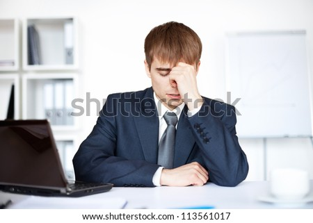 Tired young business man with problems and stress in bright office