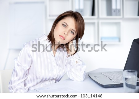 Tired young business woman in bright office